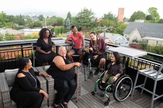 Overhead shot of six disabled people of colour at a rooftop deck party - Disabled and Here