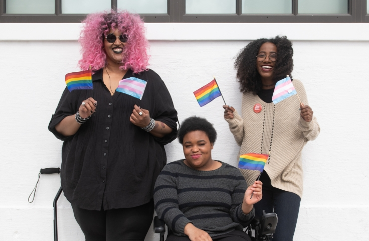 Three Black and disabled folx smiling and displaying mini flags - Disabled And Here