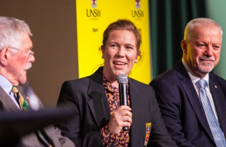 Alex Blackwell speaks into a microphone. Alex sits in front of a UNSW banner and is seated in between two men.