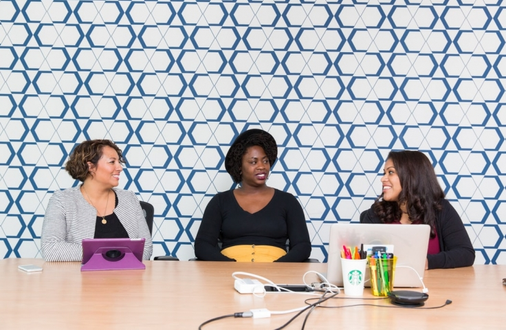Three women discussing flexible work and leave options