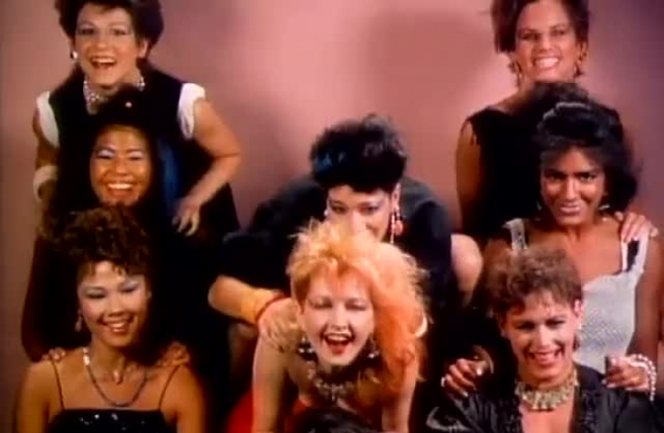 Still image from Cyndi Lauper's 'Girls Just Wanna Have Fun' video clip. Three rows of three women dancing and laughing.
