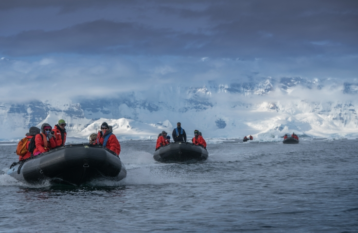 People on boats in Antarctic waters. The people are wearing red jackets.